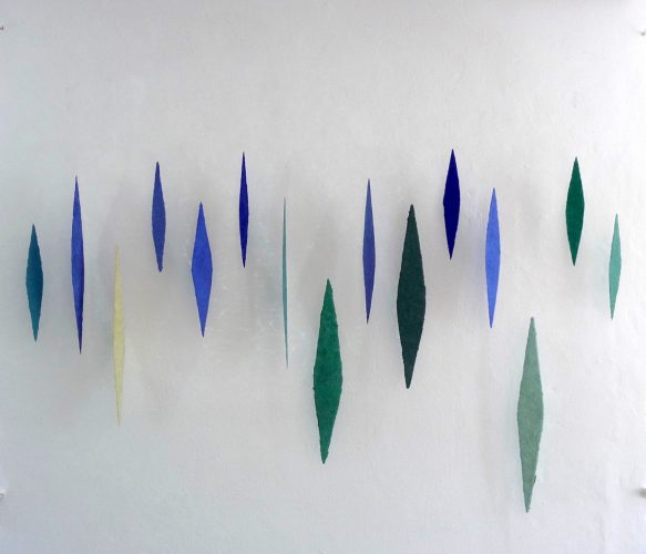 Die 15 Lanzetten, geschöpft aus blauen und grünen Mineralien und Zellulose, sind ein schwebendes und in ihrer Bewegung veränderliches Objekt vor der Wand.