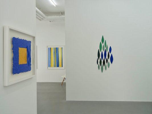 Grüner Jaspis ist ein Werk von Helmut Dirnaichner aus dem Jahr 1990 mit blattförmigen Elementen aus Jaspis, Azurit, Malachit und Zellulose geschöpft zu sehen in Galerie Renate Bender, München, 2019 in der Ausstellung Erde Stein Pigment